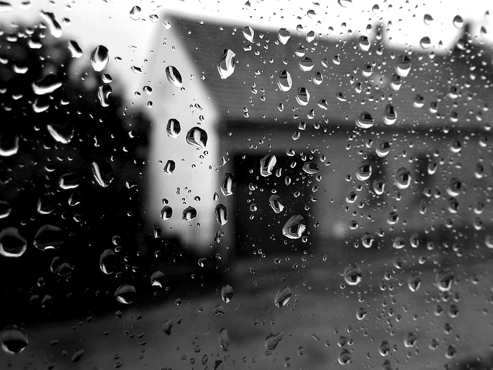 Black and white image of raindrops on a window with a blurred image of a house with a tin roof visible. Used to depict the story title 'tin roof', an exploratory scene from the midpoint of my work in progress novel