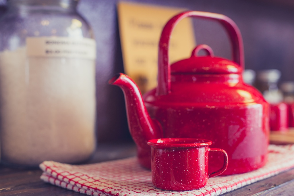 Photo of a kitchen bench with red kettle and mug to illustrate a three line tale brewing an aphrodisiac
