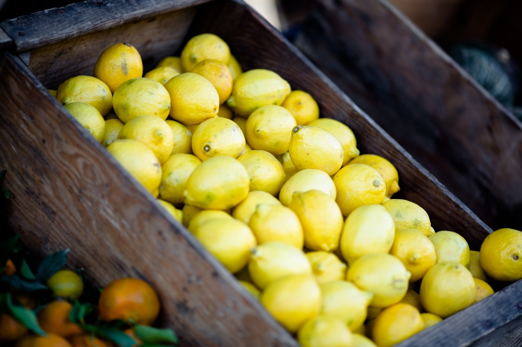Photo of lemons in a crate at a market stall for a flash fiction story on observing strangers
