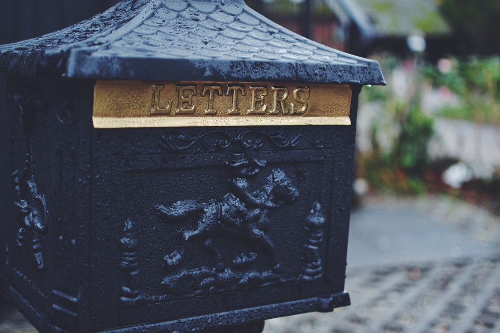 photo of a wrought iron mail box with a motif featuring a rider on horse back prompting a flash fiction story