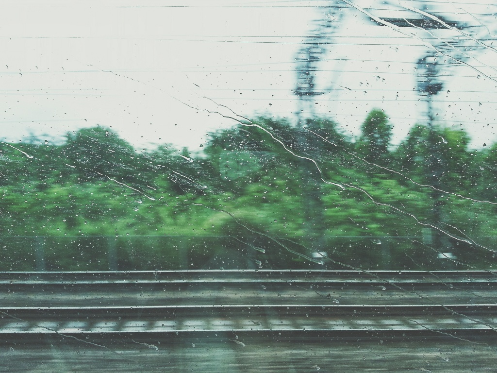 Photo of a rainy view through a train window- prompt for a flash fiction story three line tale