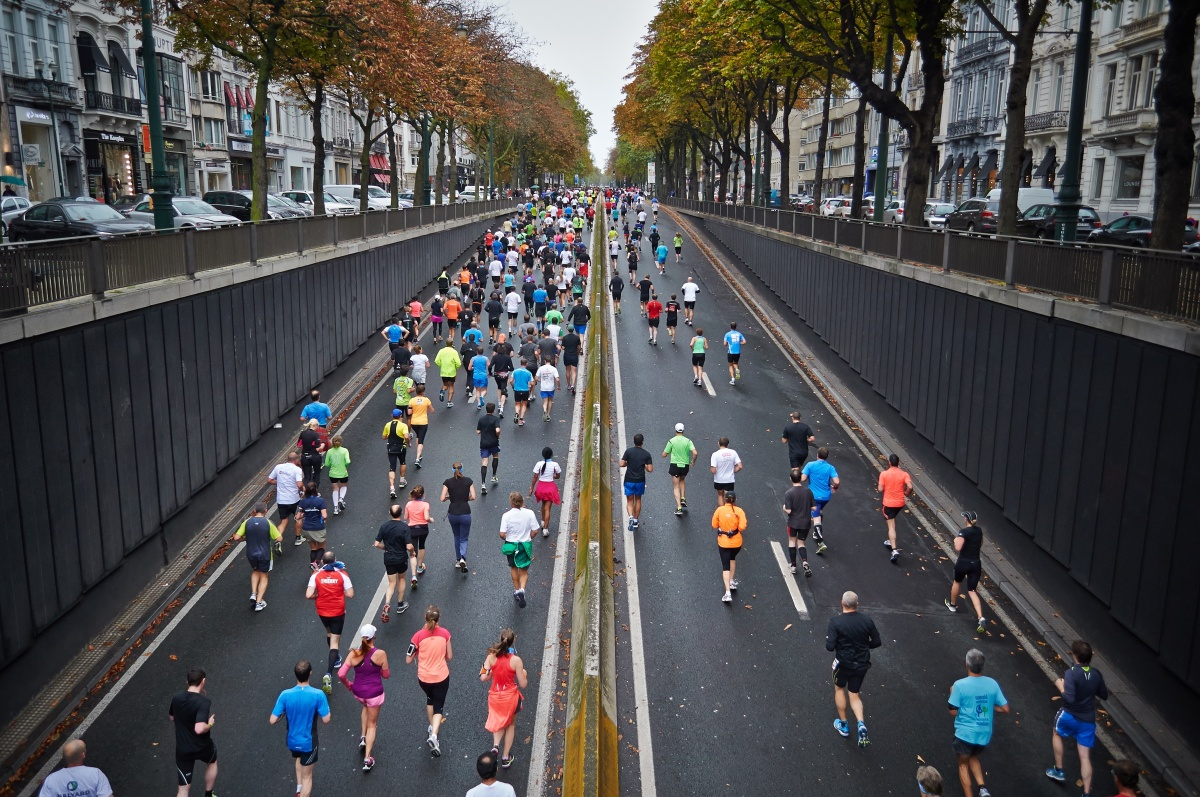 photo of runners on a multi lane road running in the same direction - prompt for a flash fiction story on peak energy