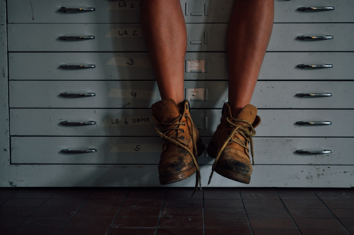 Image of worker's legs and work boots suspended off ground with office filing cabinet background- prompt for flash fiction
