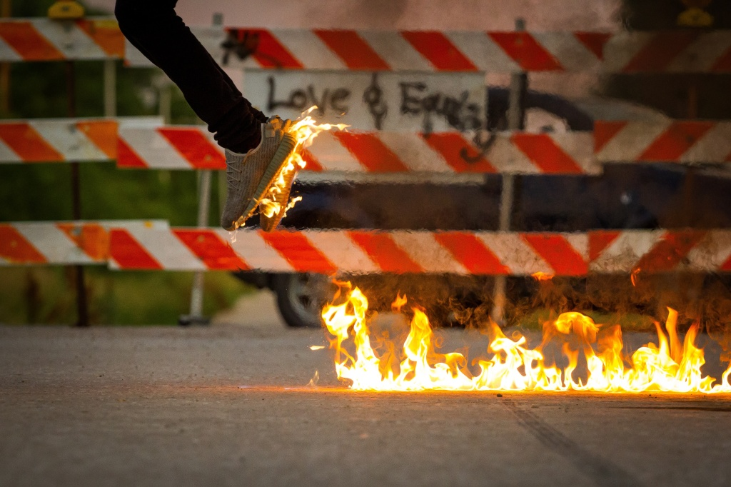 Photo of an airborne person with feet on flames, leaving a burning road, used as prompt for microfiction