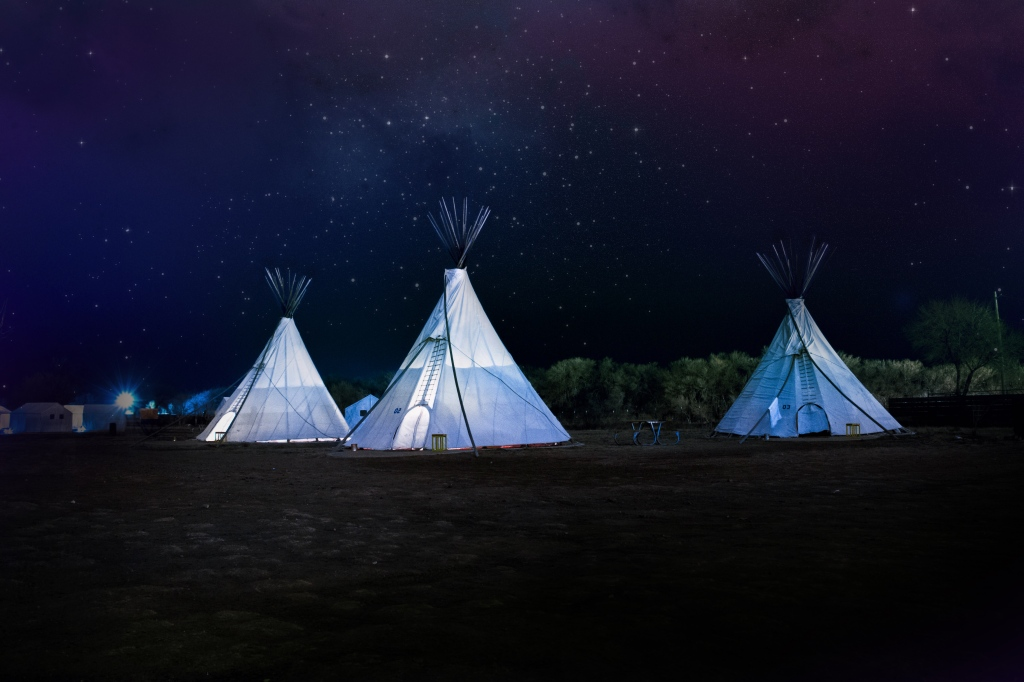 Photo of three illuminated tents in a backdrop of starry night sky used as a micro fiction writing prompt