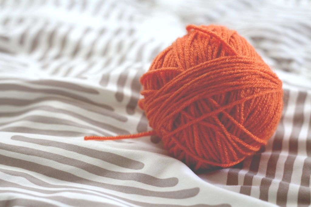 Orange ball of wool, yarn on a bed used as a prompt for creative writing: flash fiction/microfiction