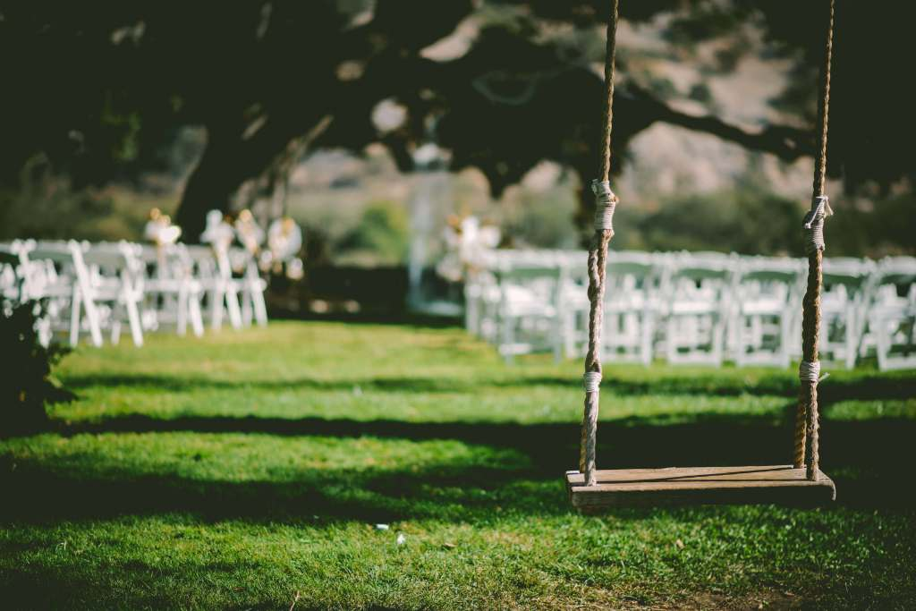 Photo of an outdoor wedding setting and a swing, green lawn used as a microfiction writing prompt
