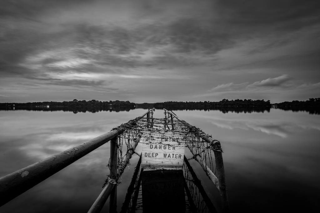 Photo by Sean Tan, used for three line tales week fifty one, microfiction prompt. Warning of deep water on a pier.