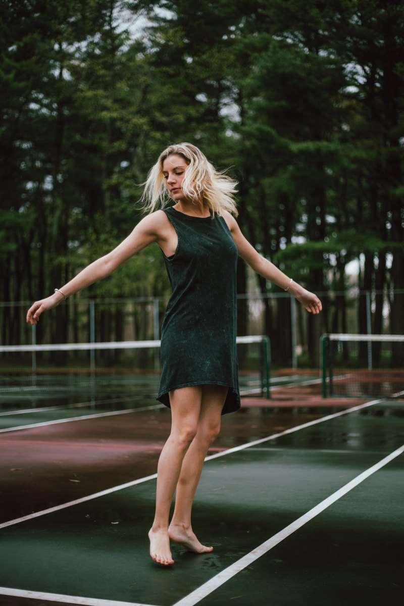 Photo of a woman whimsically dancing on wet tennis court- used as prompt for three line tales microfiction