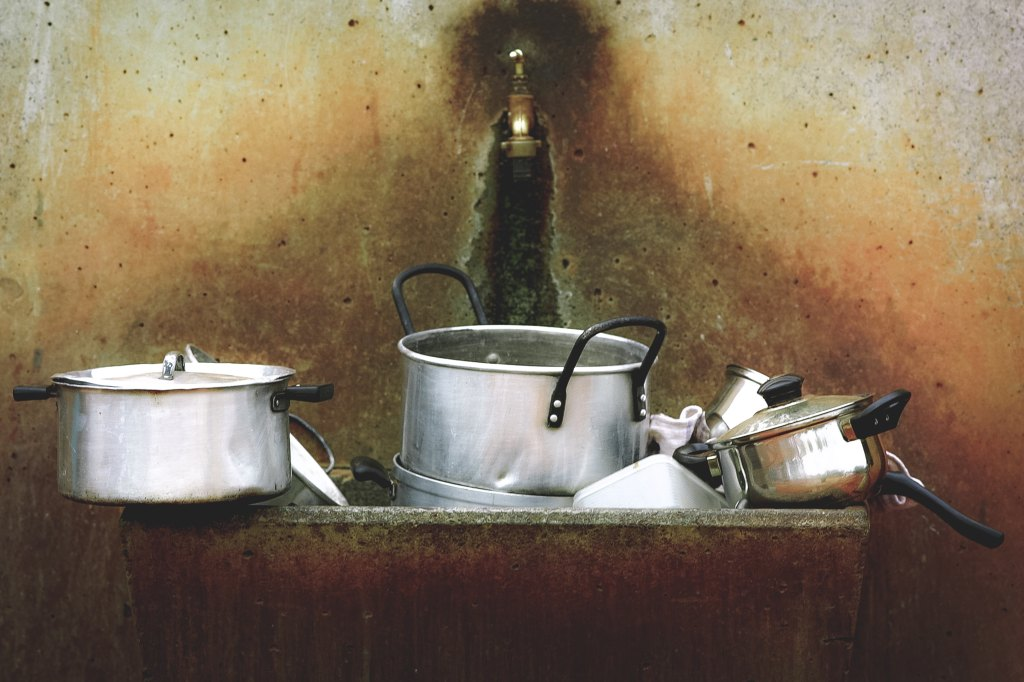 Photo of a pile of dirty dishes in a small sink with a single tap, used as a micro fiction prompt