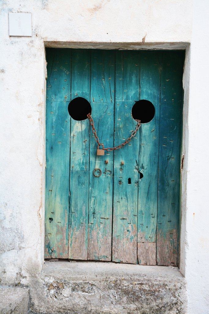 Photo of a wooden door on a stone building, shut with a chain and padlock. Used as photo prompt for flash fiction.