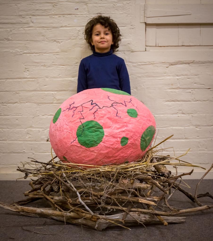 Birthday boy with giant dinosaur egg pinata on a nest