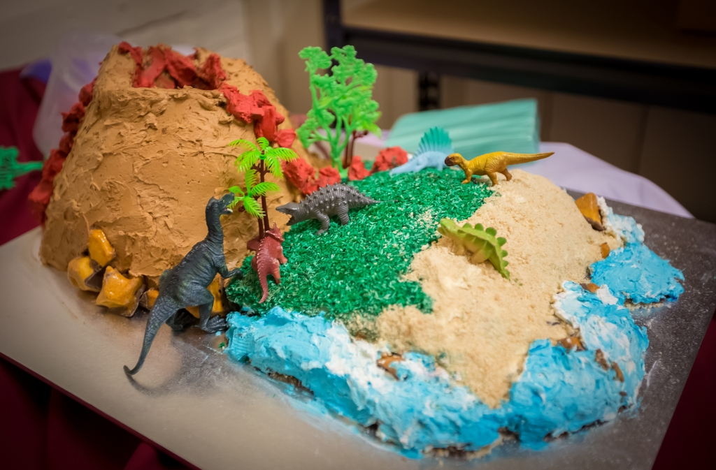 Birthday cake designed with volcano, grass, sand and surf and dinosaur figurines.