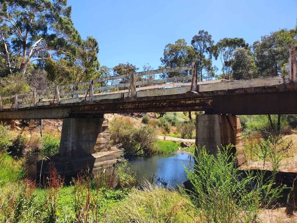 Photo of an old bridge over a shallow creek. The banks have various green shurbs and trees and the sky is blue.